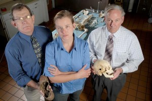 Coconino County AZ Cold Case Unit members Joe Sumner, Amy Kelly and Chuck Jones stand with the skull of an unidentified set of remains that bears the entrance wound from a single gunshot. The remains were originally found below Shoshone Point at the South Rim of the Grand Canyon in 1933. (photo courtesy of Jake Bacon/AZ Daily Sun)